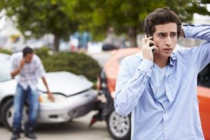 young man on cellphone after car crash