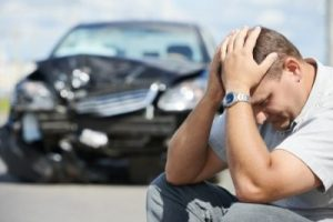 upset man sitting in front of a car wreck, injury lawyer
