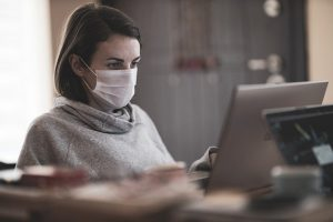 Woman wears mask working at office