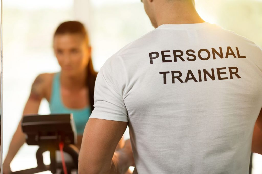 Young lady with a personal trainer at gym