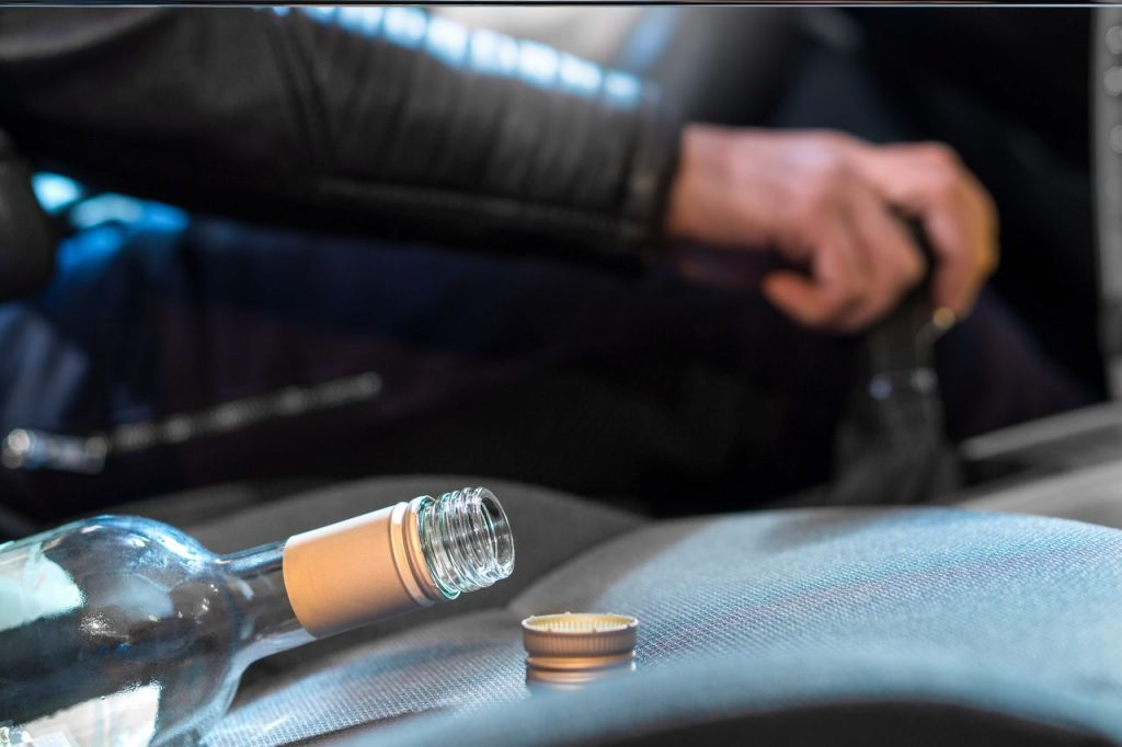 Car driver with an empty bottle of wine, drunk driving