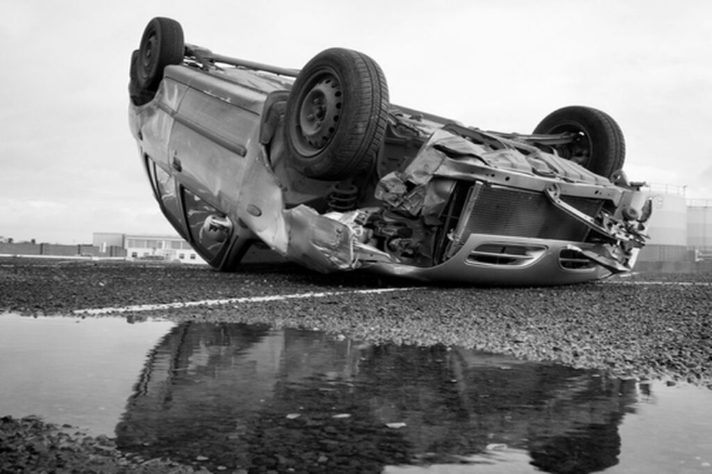 black and white image of a car rolled over on a poor road