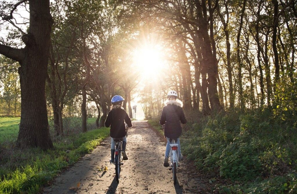 Two girls with helmet are riding bicycles